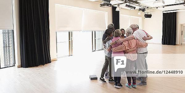 Active seniors bonding  hugging in circle in exercise studio