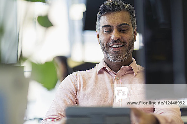 Smiling businessman working at digital tablet in office