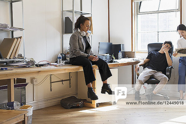 Creative businesswoman with headphones sitting on desk in office