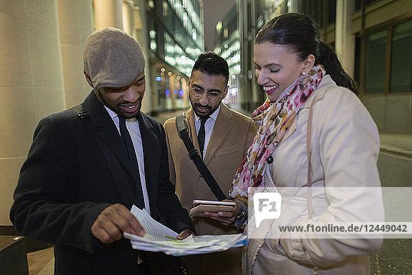Business people reviewing paperwork on urban sidewalk at night