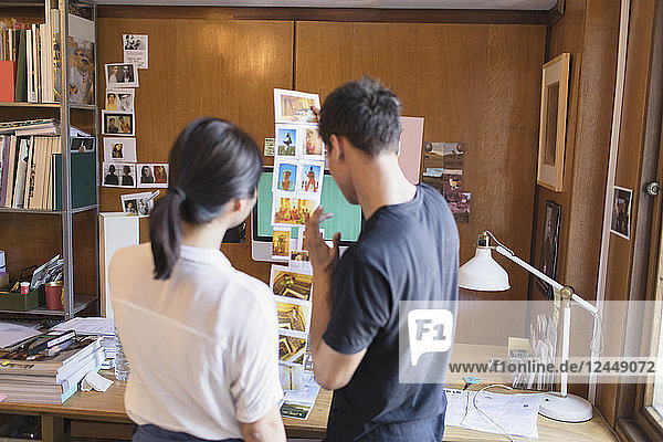 Creative designers reviewing photograph proofs in office