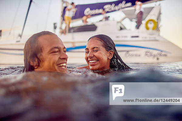 Happy young adult couple swimming near catamaran in ocean Happy young adult couple swimming near catamaran in ocean
