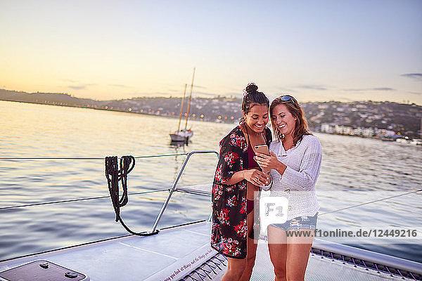 Young women using smart phone on catamaran