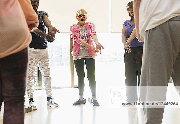 Active seniors stretching wrists in exercise class