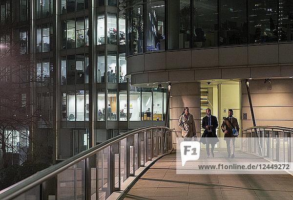 Business people walking on urban pedestrian bridge at night