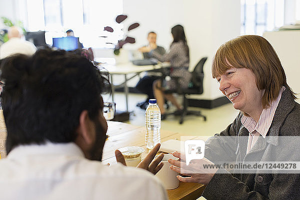 Smiling businesswoman talking with colleague in office