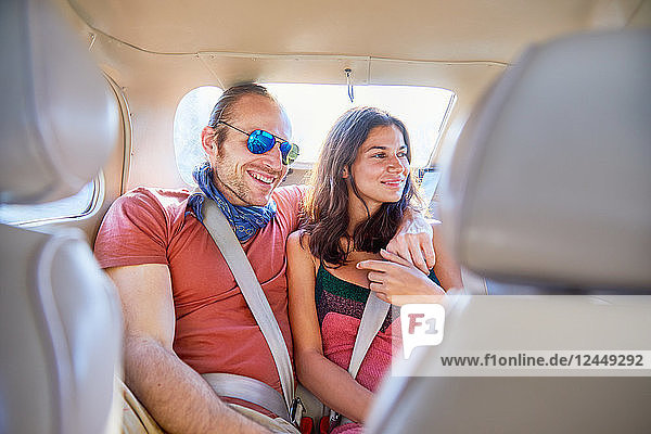Affectionate couple riding in back seat of car