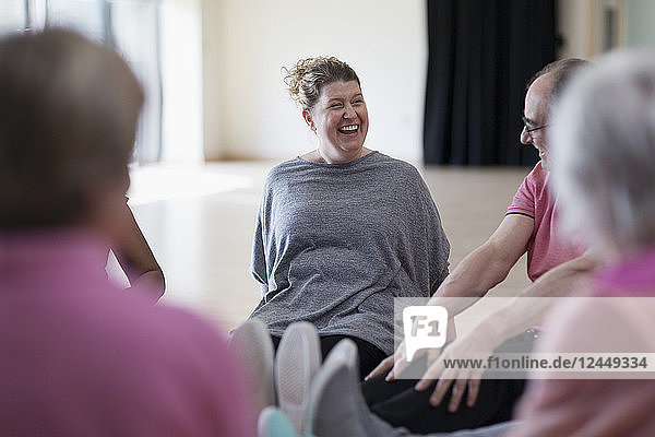 Laughing instructor and active seniors stretching legs in exercise class