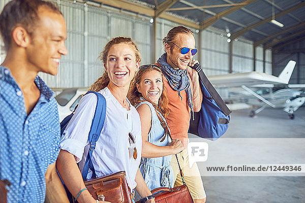 Happy friends walking in airplane hangar