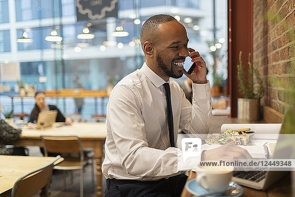 Smiling businessman talking on smart phone  working in cafe