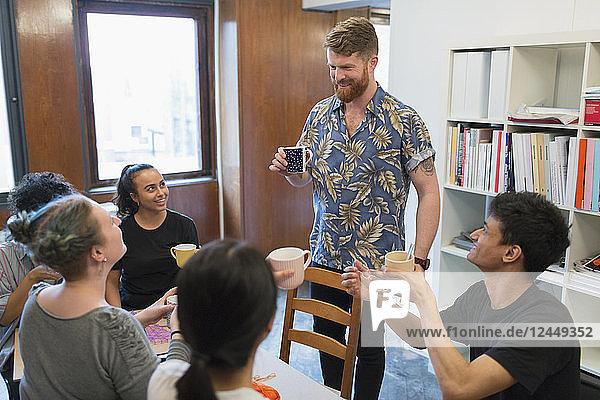 Creative business people enjoying coffee and tea in office