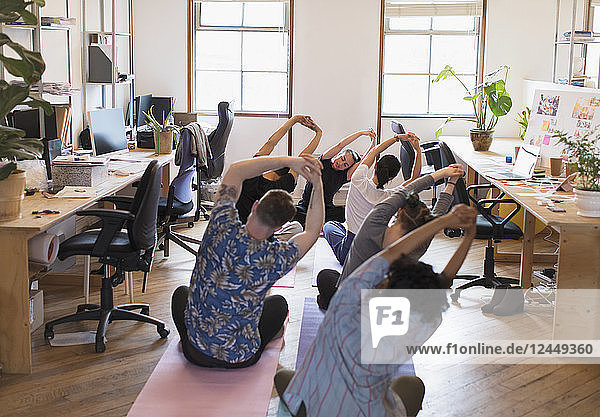 Creative business people stretching  practicing yoga in office