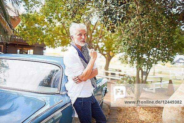Portrait confident man biting tip of eyeglasses at car
