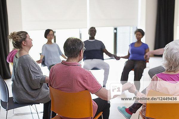 Serene active seniors holding hands  meditating in circle