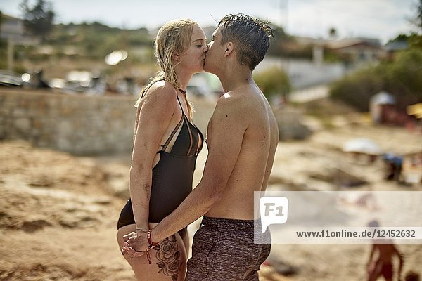 Greece  Crete  Chersonissos  couple in swimwear at beach  kissing  love  relationship  holiday  lovers