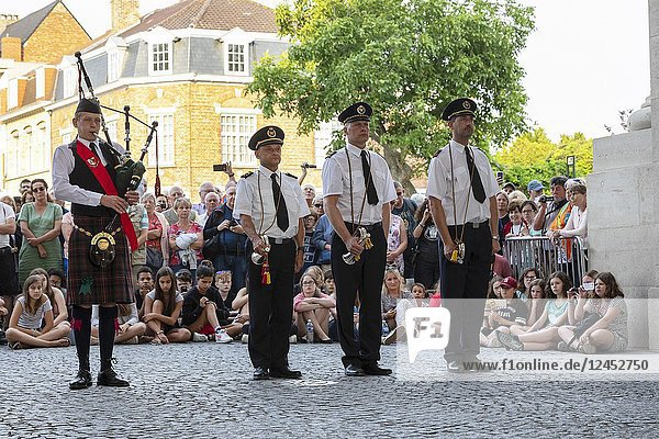 Three buglers standing to attention while a lone piper plays a lament at the Menin Gate war memorial  Ypres  Belgium.