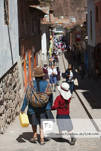 Indigenous woman in traditional dress walking with her daughter in the narrow streets of the Pisac town  Cusco Region  Peru  South America