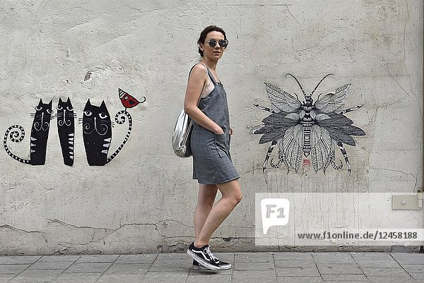 Young stylist woman wearing one of her dress  posing in a street of the District of Kazimierz  Krakow  Malopolska Province (Lesser Poland)  Poland  Central Europe.
