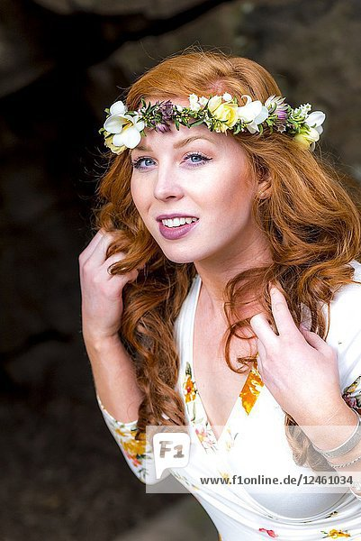 A pretty 25 year old redheaded woman wearing a crown of flowers and pulling her hair looking at the camera  outdoors.