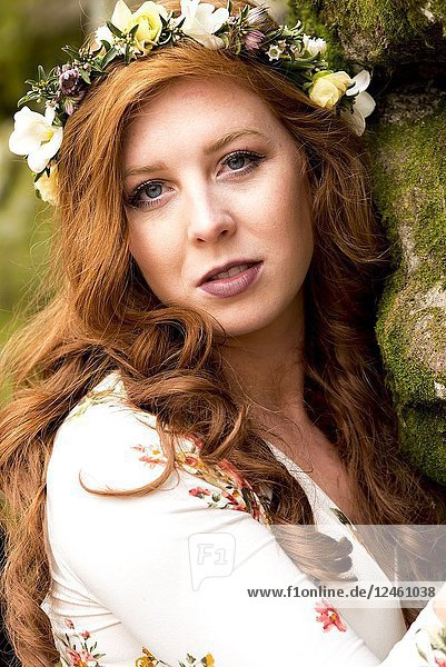 A portrait of a pretty 25 year old redheaded woman wearing a crown of flowers looking directly at the camera  outdoors.