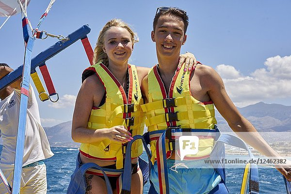 Couple on boat wearing lifejackets  ready for parasailing. Chersonissos. Crete  Greece.