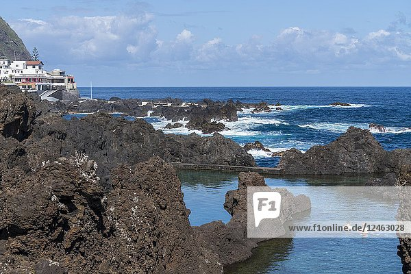 Three men bathing in the natural pools of Porto Moniz  Madeira region  Portugal.
