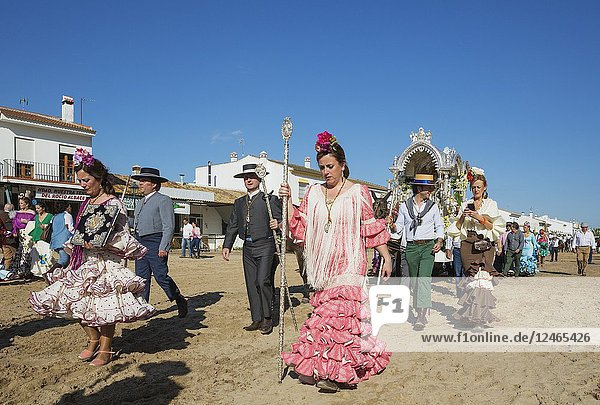 Women wearing beautifully coloured gypsy dresses and dressed up men during the annual Pentecost pilgrimage of El Rocio. Huelva province  Andalusia  Spain.
