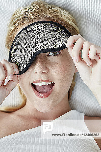 Portrait of young woman with eye mask covering one eye.