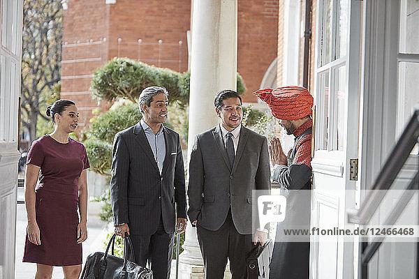 Concierge in turban greeting businesspeople