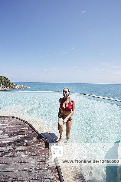 Young woman wearing red bikini walking out of swimming pool