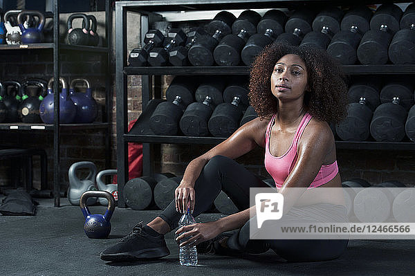 Young woman sitting with water bottle beside dumbbell rack