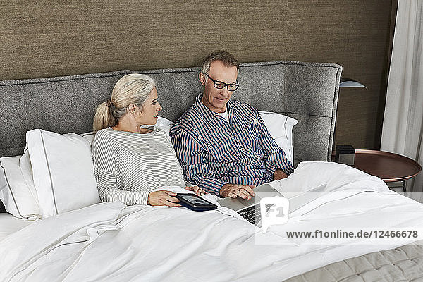 Mature married couple using laptop together.