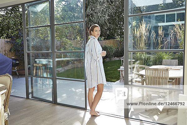 Mid adult woman standing at open door.