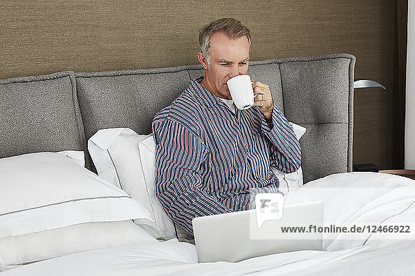 Mature man using laptop in bed.
