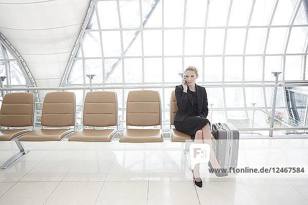 Businesswoman with luggage at Suvarnabhumi Airport in Bangkok
