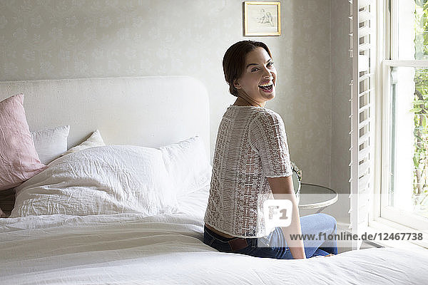 Smiling mid adult woman sitting on her bed.