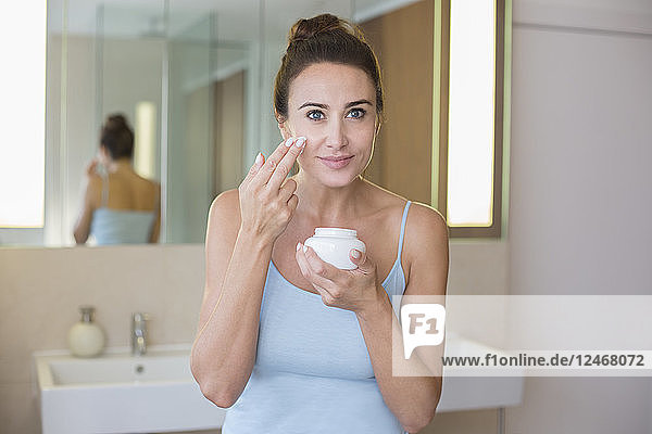Mid adult woman applying moisturiser in bathroom.