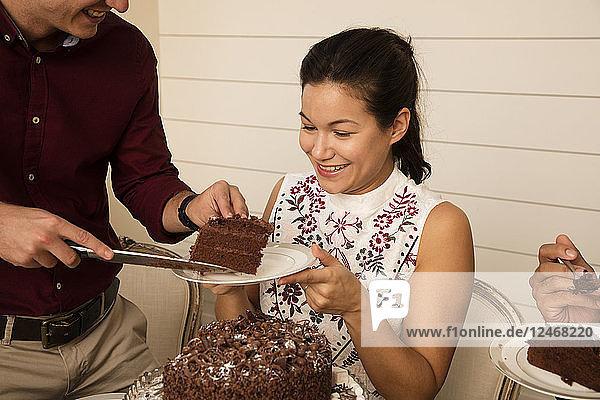 Friends celebrating with chocolate birthday cake