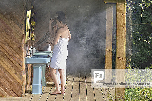Young couple brushing their teeth at outdoor sink.