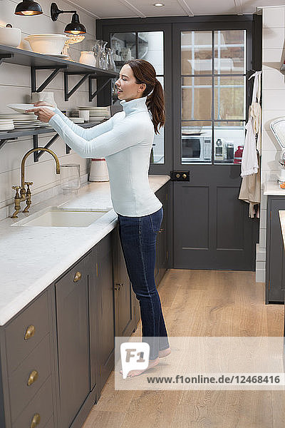 Mid adult woman taking plate from kitchen shelf.