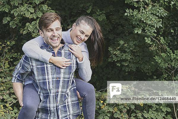 Young man giving girlfriend piggyback ride.