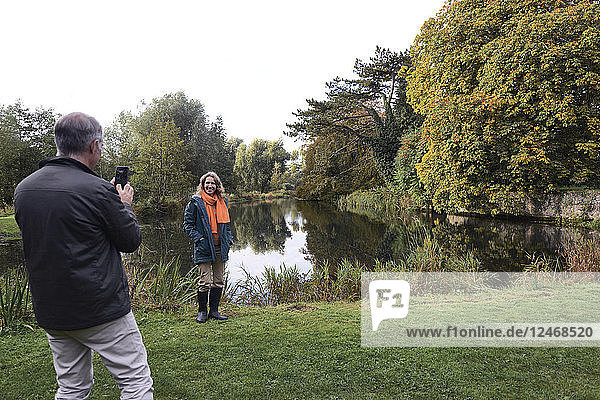Mature man taking photograph of wife standing beside river.