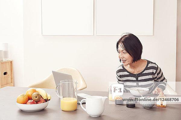 Senior woman using laptop at breakfast table