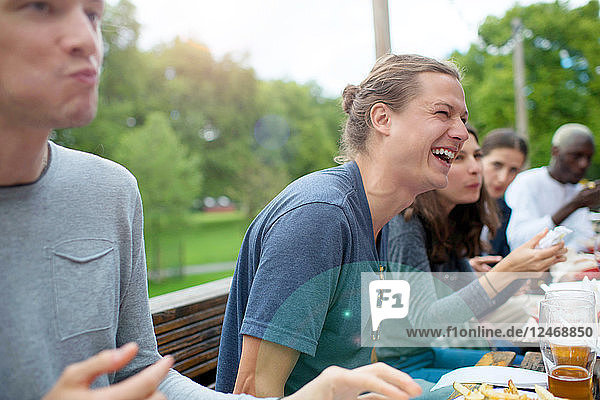 Young man laughing with friends at outdoor restaurant