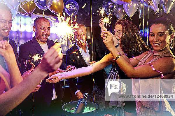 Group of friends celebrating with sparklers at nightclub