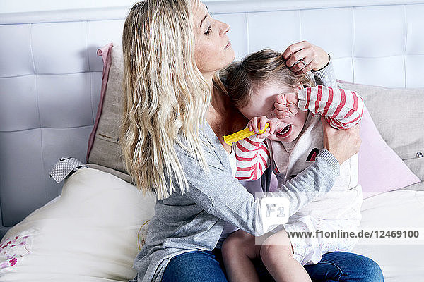 Mother with crying daughter on bed