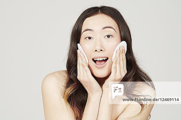Young woman wiping face with cotton pad