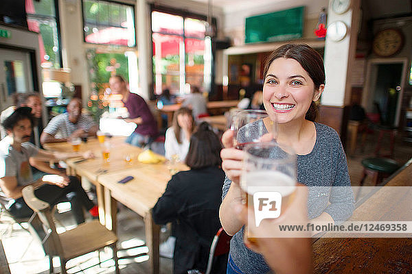 Young woman making celebratory toast at bar