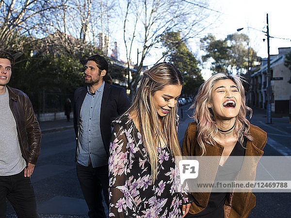 Friends laughing together in street