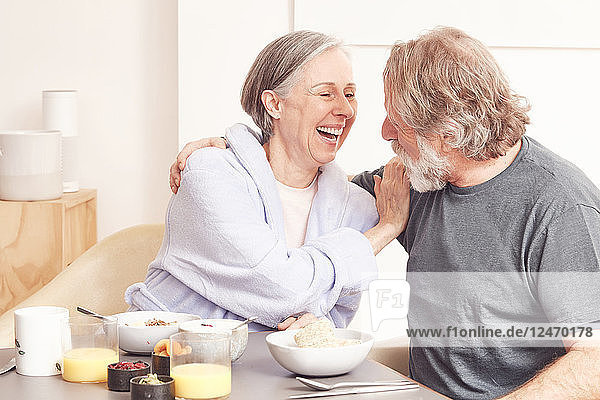 Senior couple laughing at breakfast table